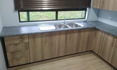 Kitchen with wooden cupboards and wooden floor